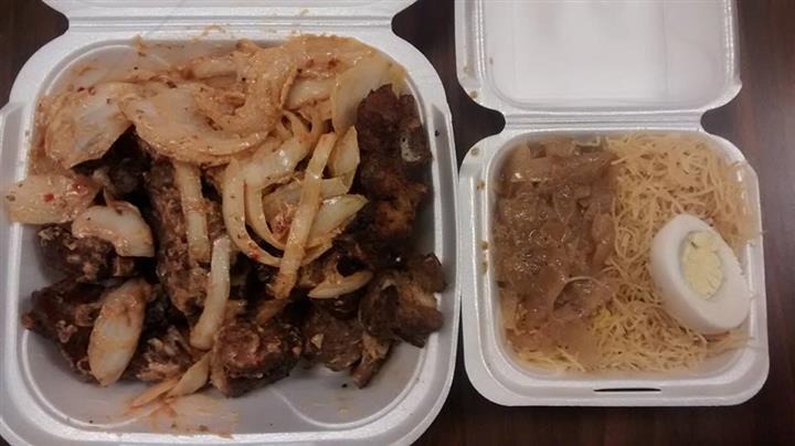 cooked meat and onions in a takeout container next to a side of noodles, egg and veggies in a takeout container