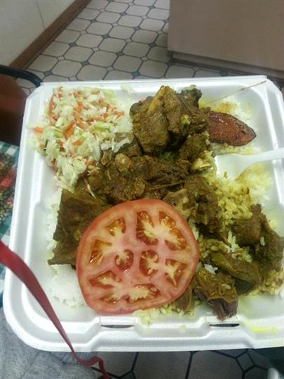 cooked meat and rice with a slice of tomato in a takeout container