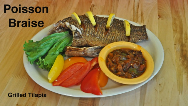 Poisson Braise (grilled tilapia) with mixed pepers and lemons on a plate