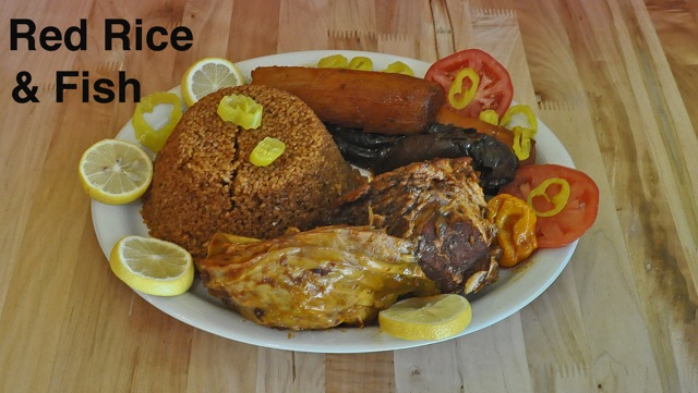 Red Rice and Fish on a plate with lemons, peppers and tomatoes around the edges of the plate