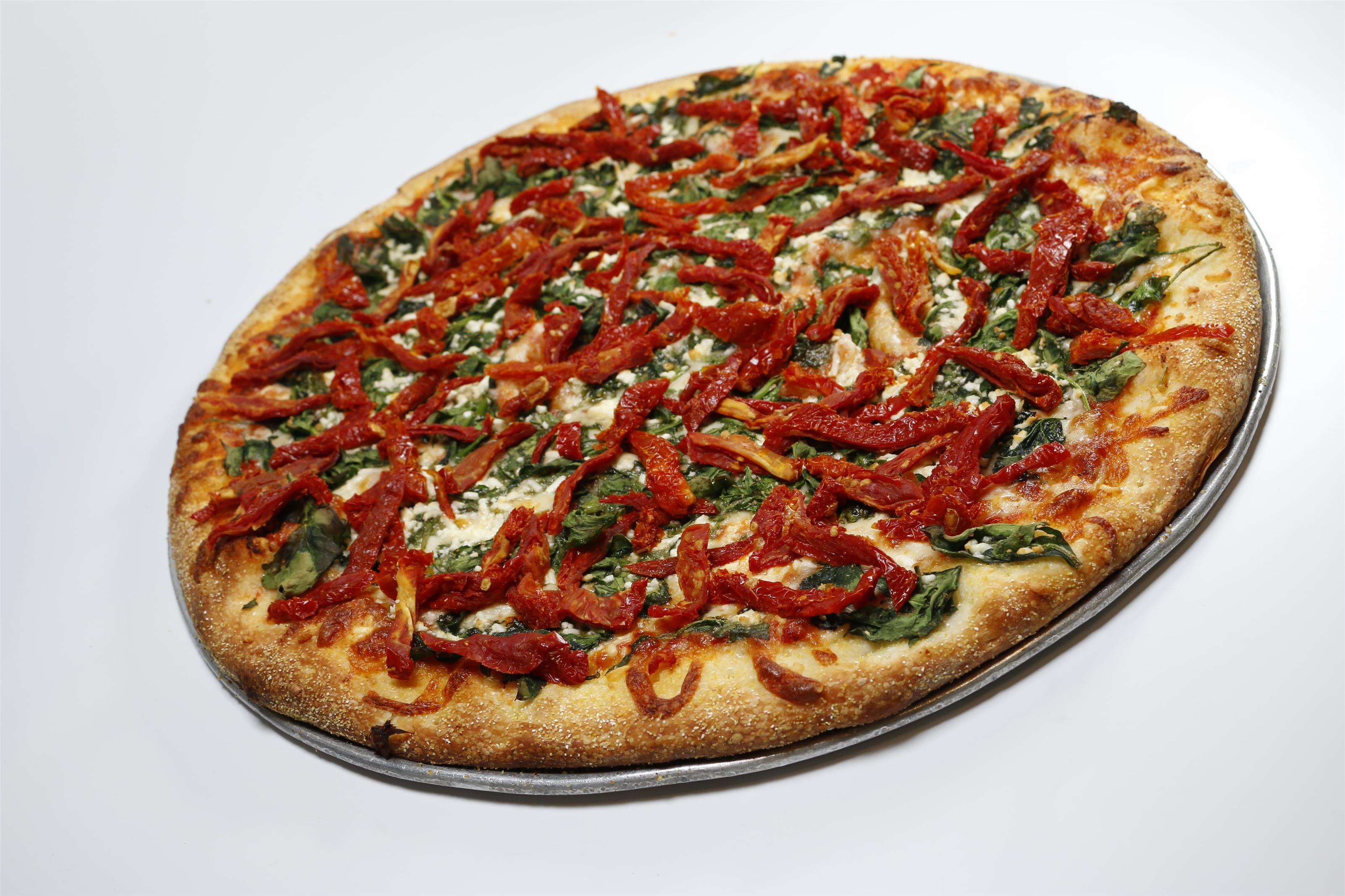 Margharita pizza with shredded red peppers, feta cheese, and shredded basil