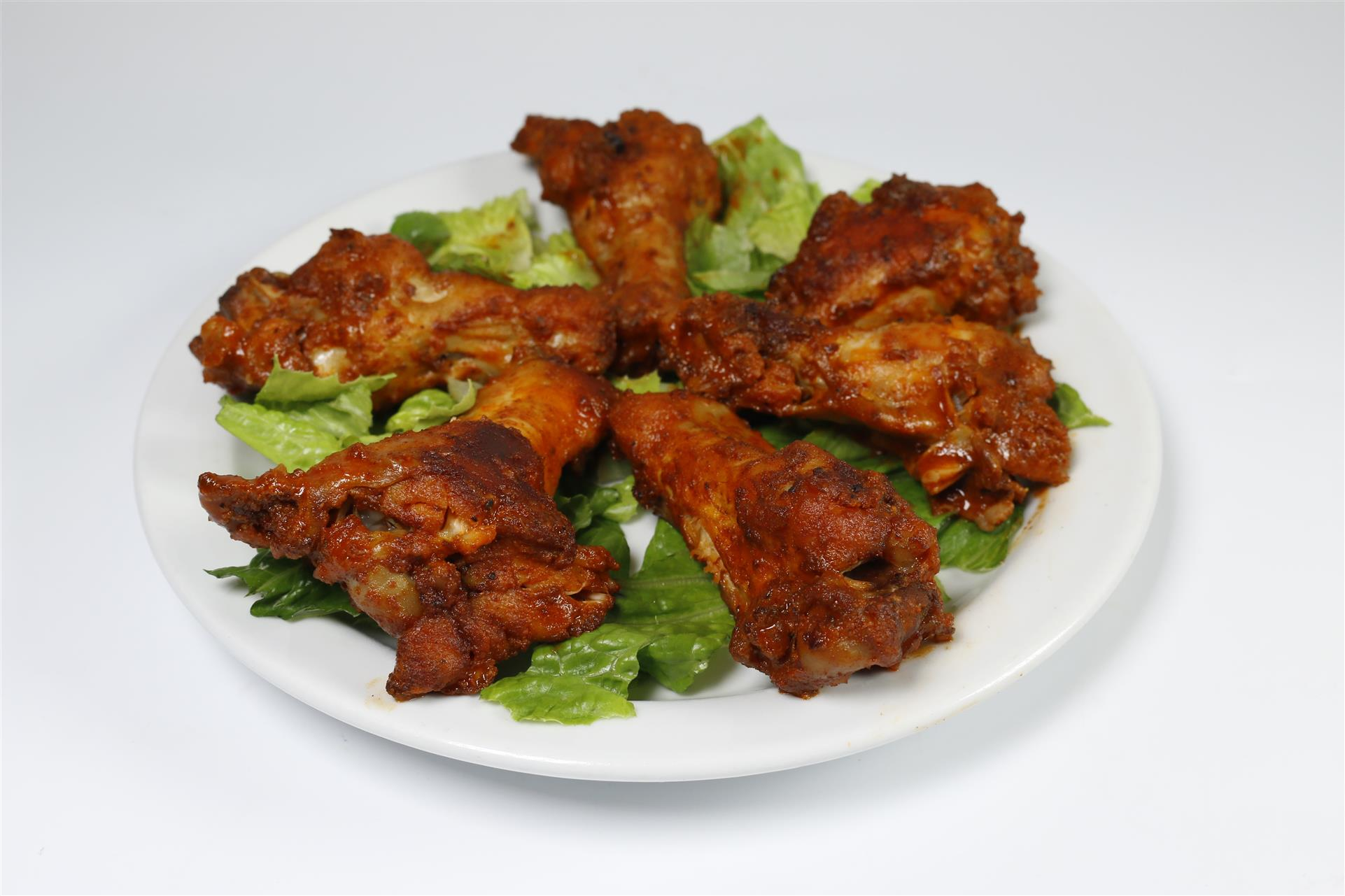 Crispy chicken wings covered in buffalo sauce on plate of lettuce