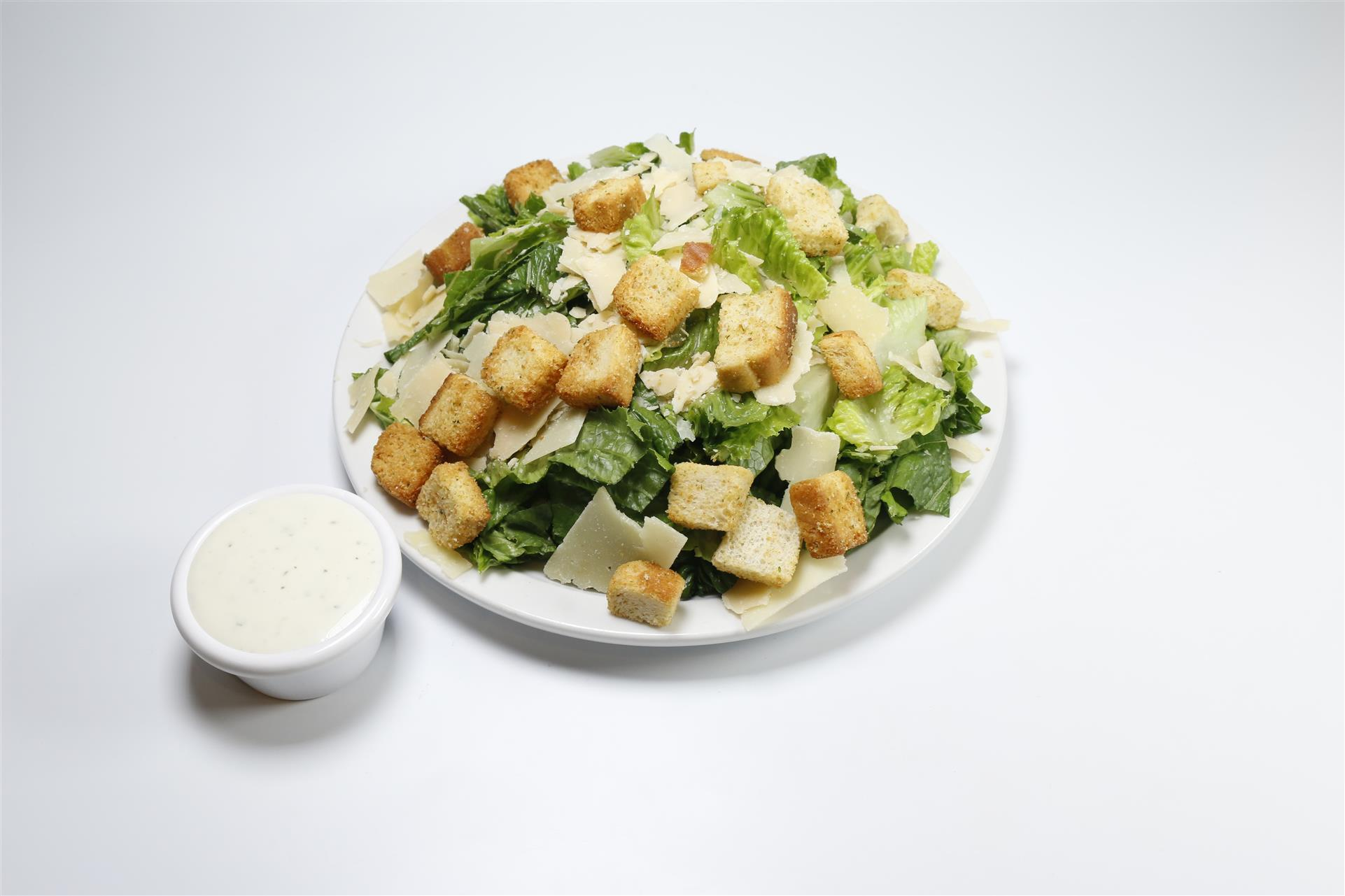 Cesar salad on white plate with croutons, shaved parmesan cheese next to cup of cesar dressing
