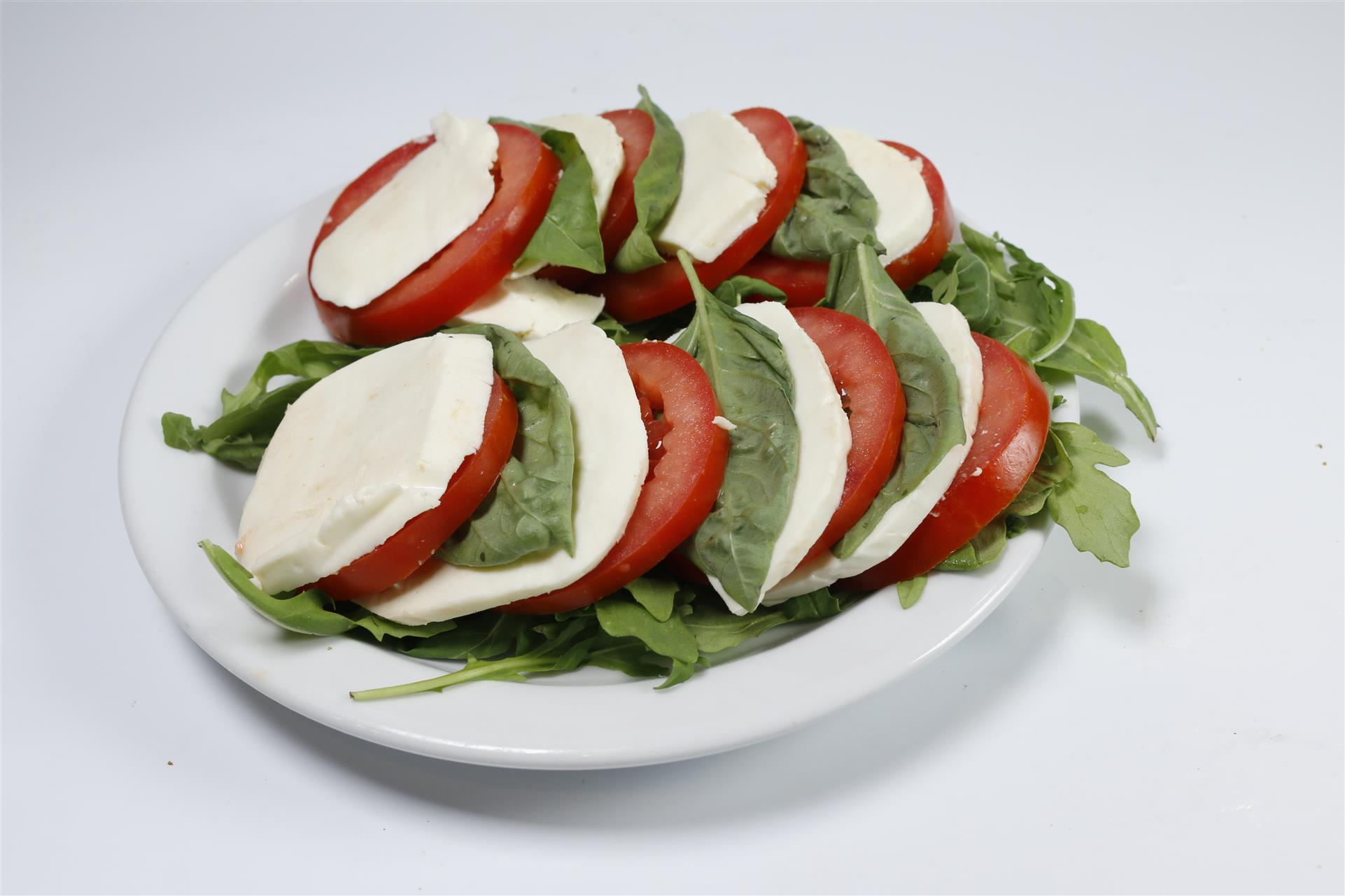 Mozzarella di buffalo, Roma tomato, fresh basil on bed of arugula.