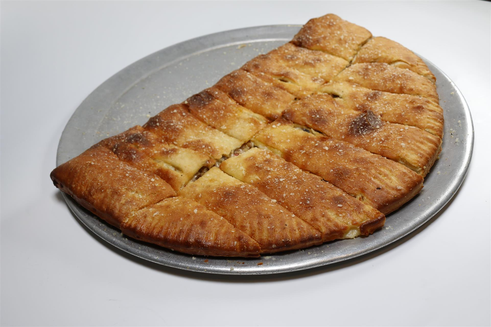 baked calzone cut into pieces on a metal tray