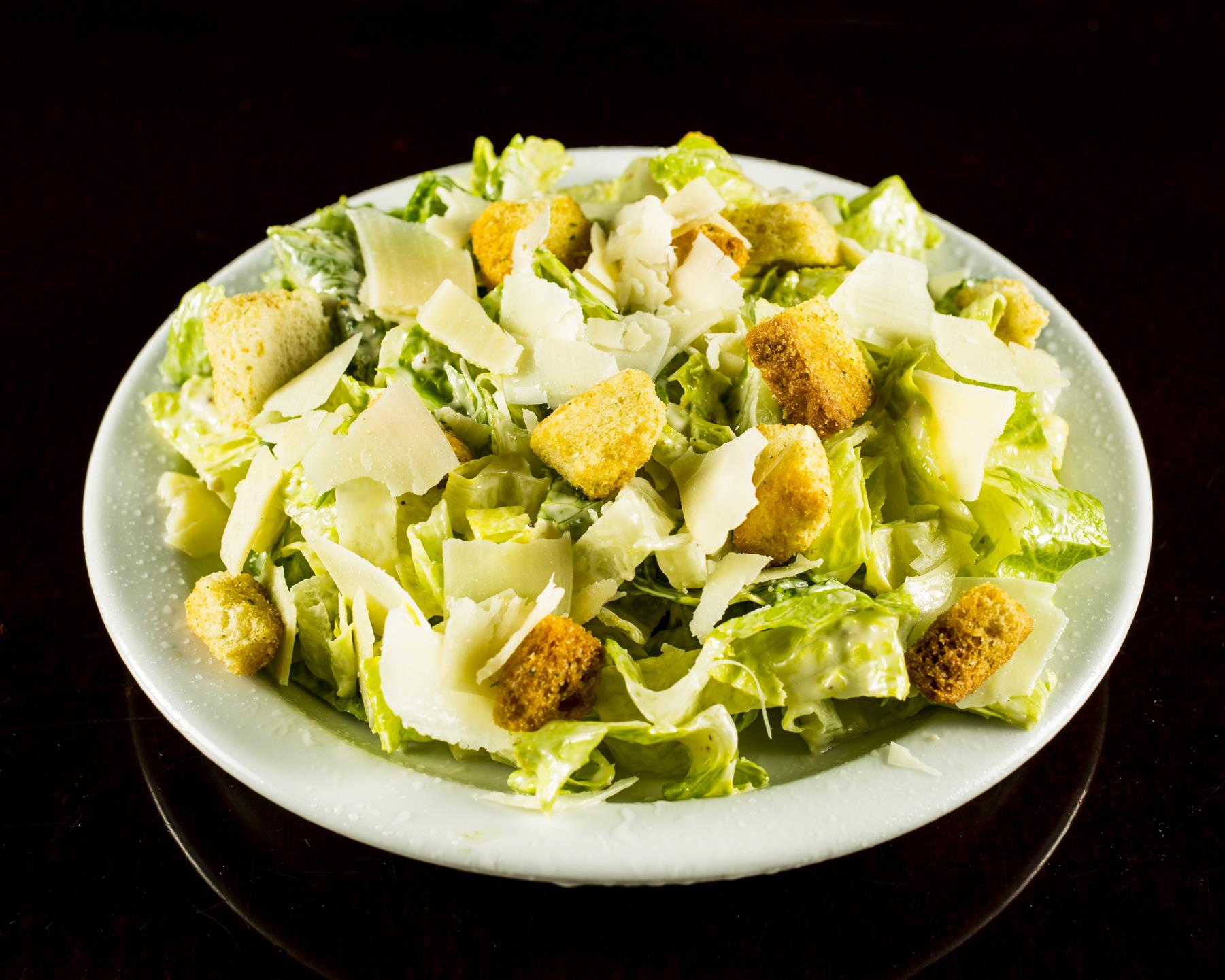 caesar salad topped with shredded cheese, croutons and dressing
