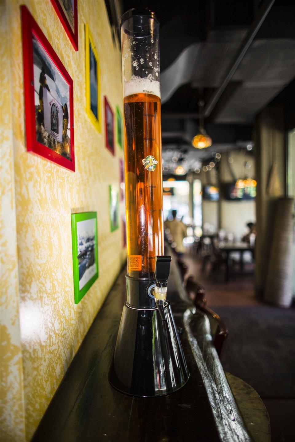 Beer tower filled with beer on wooden bar