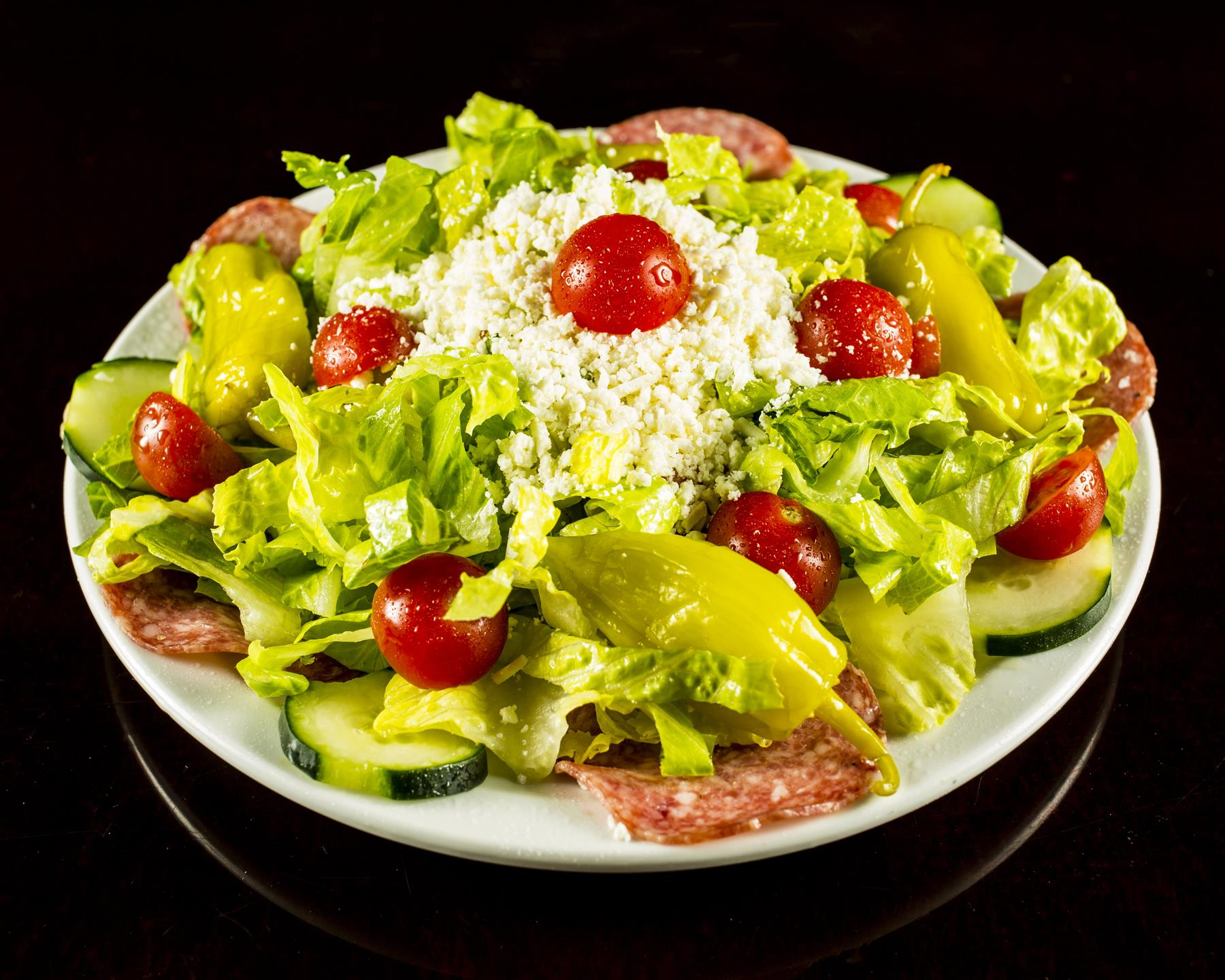 antipasto salad with green leaves, roma tomatoes, hearts of palm, greek olives, salami, ham, and mozzarella cheese
