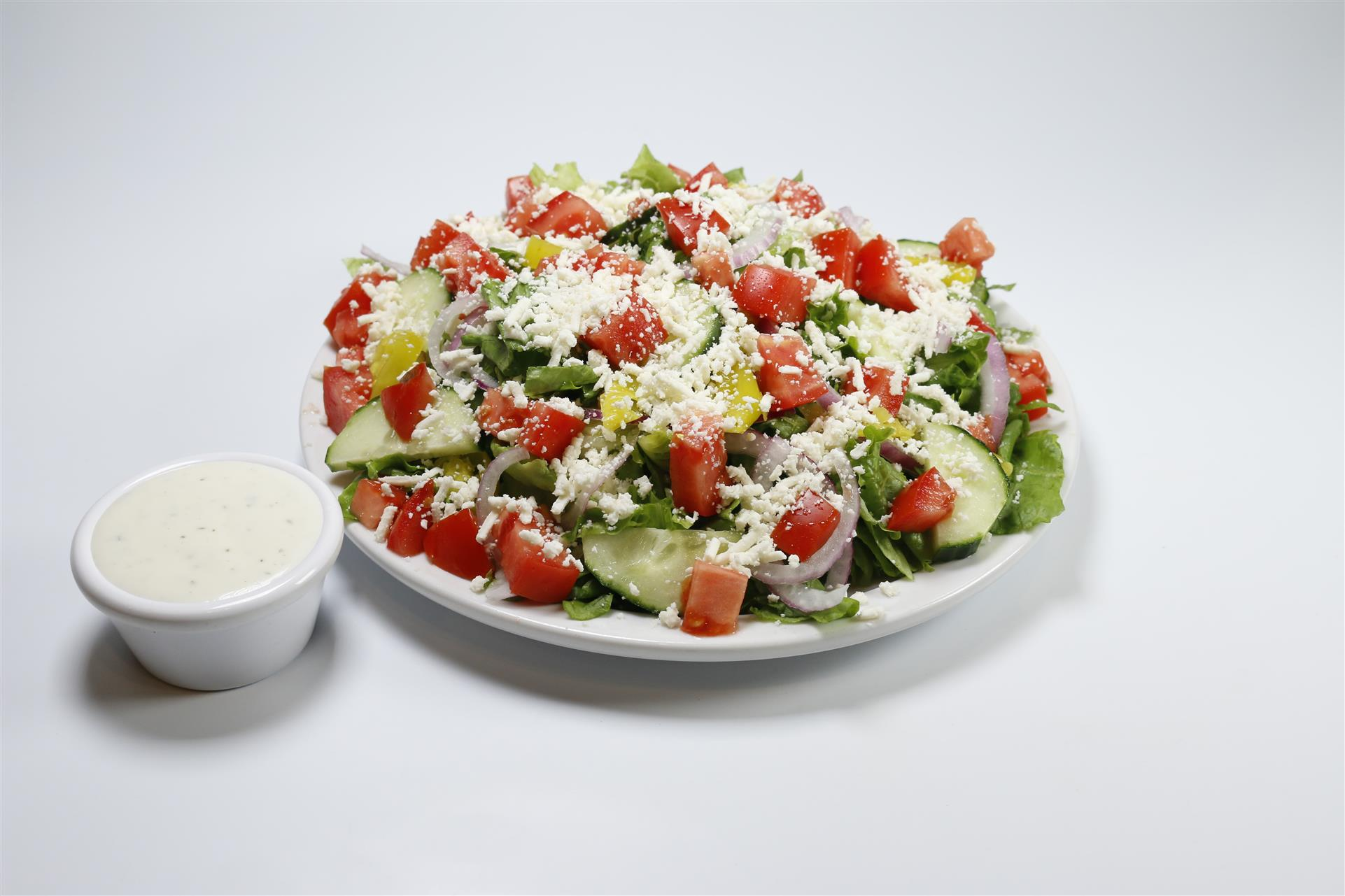 Greek Salad topped with feta cheese, tomatoes, and red onions with dressing on the side