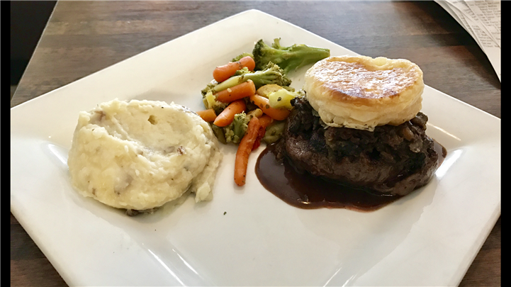 steak, mashed potatoes, puff pastry, and assorted veggies on a plate