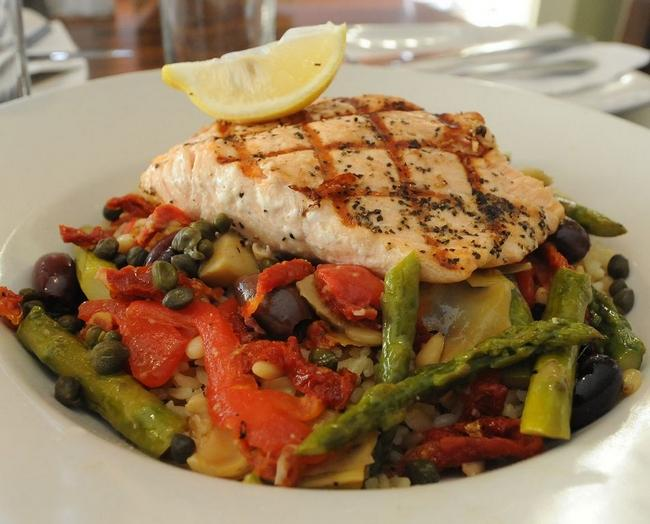grilled salmon on top of assorted roasted veggies
