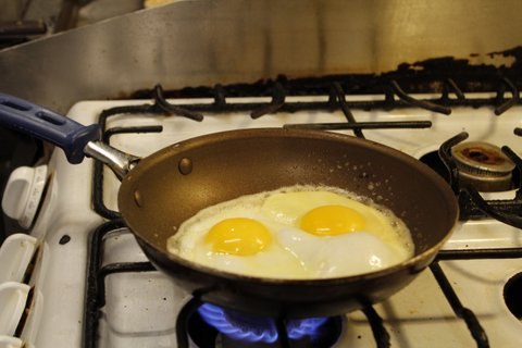 two eggs cooking on a pan