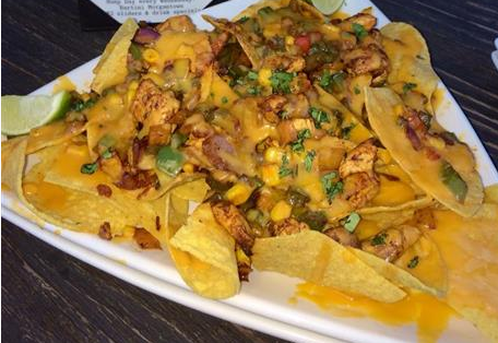 Cheesey nachos topped with corn, bell peppers.