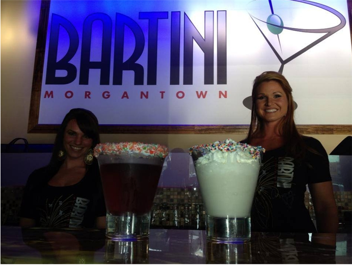 Employees behind bar, in front of bartini morgantown sign.