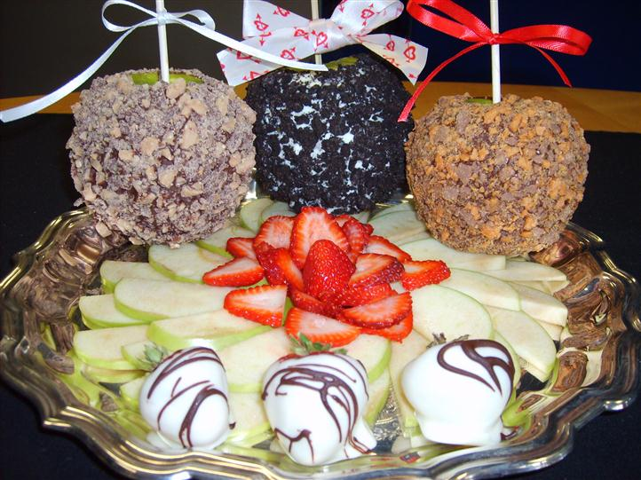 Chocolate covered apples and strawberries with cut up apples and strawberries in the middle