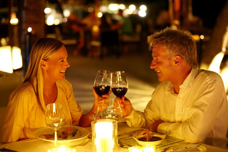 Middle-aged couple clinking red wine in glasses over candelit dinner