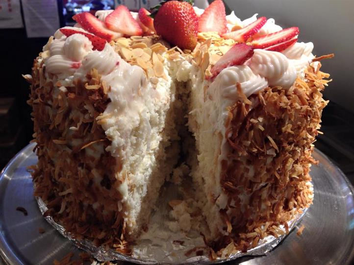 Cake with coconut outside and topped with icing, sliced almonds, and strawberries. Vanilla cake on the inside
