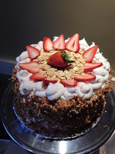 Cake with coconut coated outside, topped with icing, sliced almonds, and strawberries