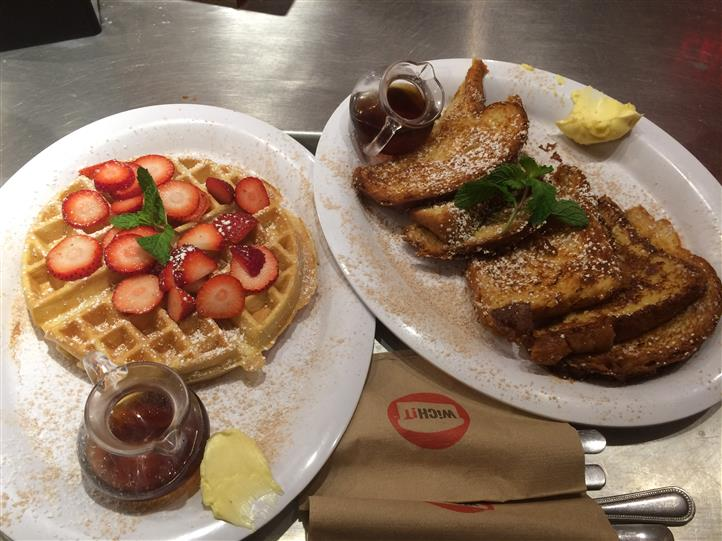 Waffle with strawberries on top and French toast with syrup and butter