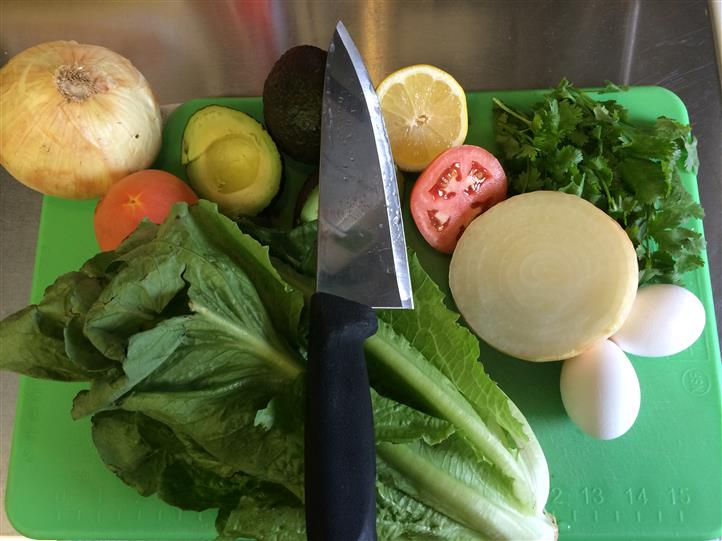 Lettuce, vegetables with a knife lying on top