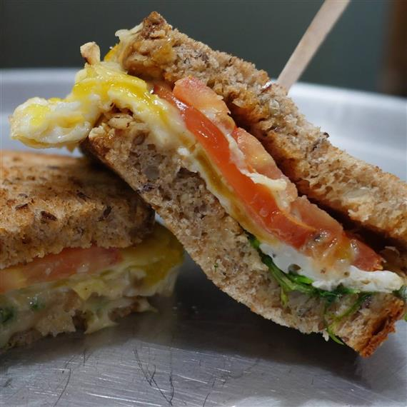 An egg sandwich with onion and spinach on whole grain bread
