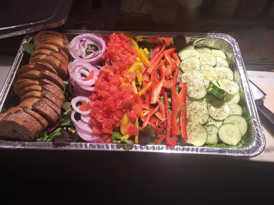Catering tray filled with lettuce, tomato, peppers, cucumbers, and a side of sliced bread
