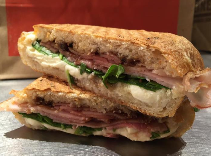 A toasted panini with ham, cheese, and spinach