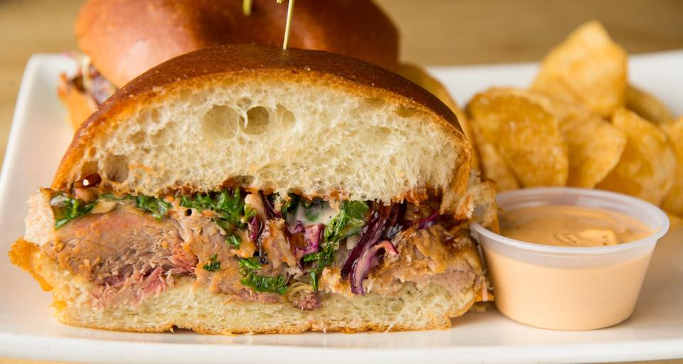 A roast beef sandwich with Russian dressing, lettuce, and cabbage