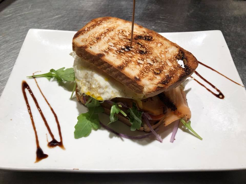 An egg sandwich with lettuce and drizzled with balsamic glaze