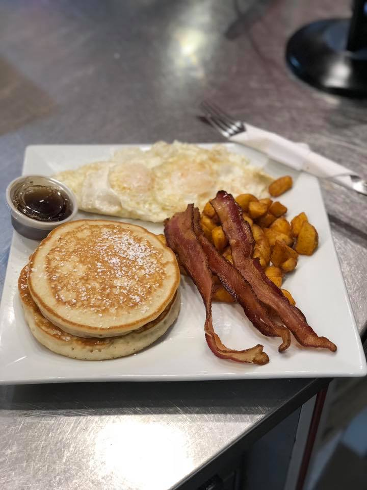 Pancakes, eggs, home fries, and bacon on a plate