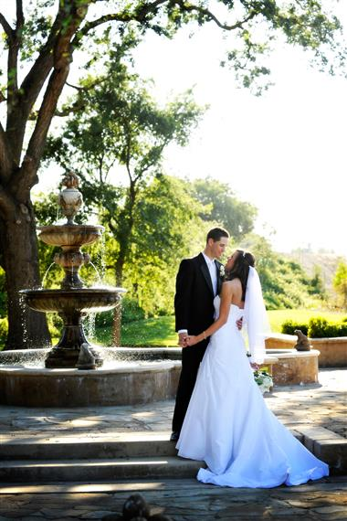 bride amd groom kissing in front of a fountain outside on a sunny day