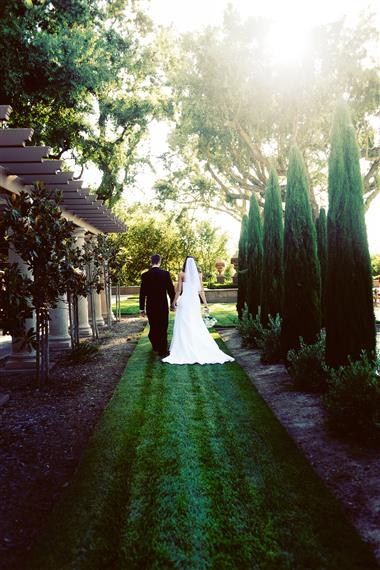 bride and room walking down an outdoor walkway framed by shrubbery and columnswith hanging plants