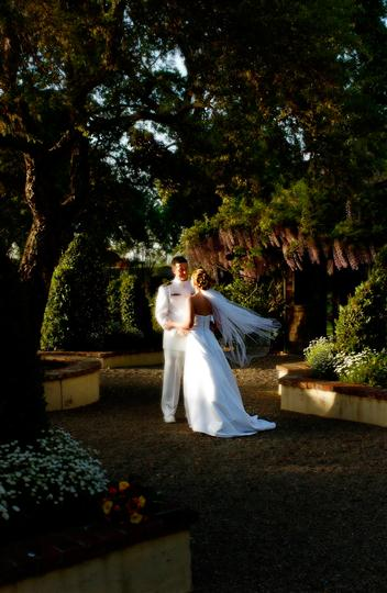 bride and groom kissing outside beneath trees