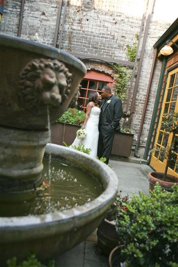 Bride and groom in background, fountain in foreground