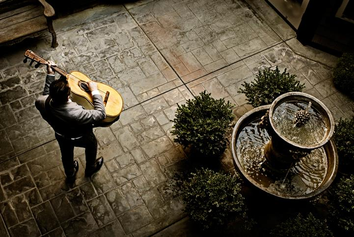 Man playing guitar in courtyard, overhead shot