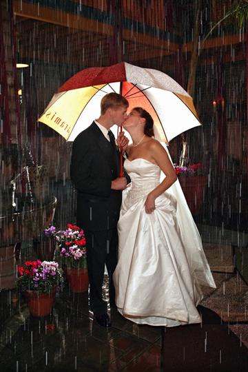 Bride and groom standing under umbrella in the rain