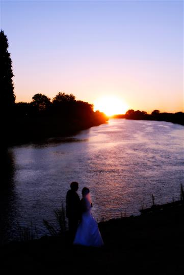 Bride and groom looking out at water, sunset