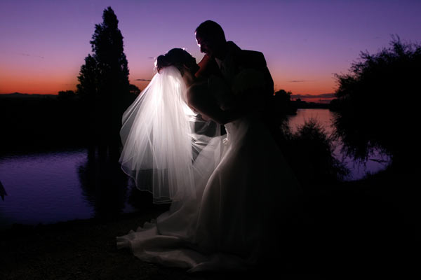 Bride and groom by water, sunset