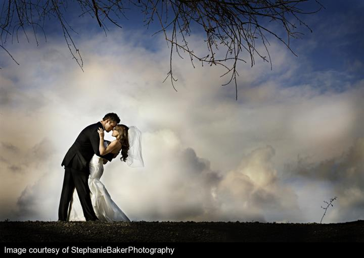 Bride and groom posing with clouds in background