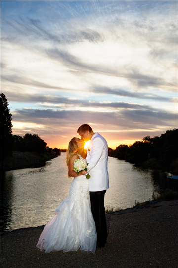 Bride and groom kissing by water, sunset