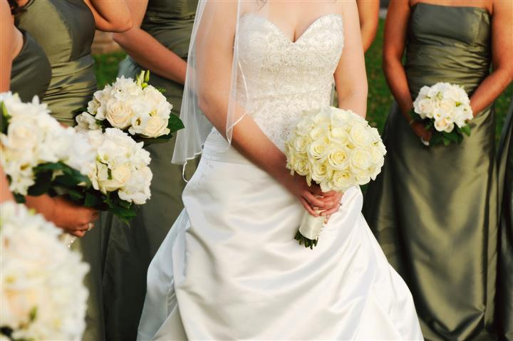 Bride holding flowers with bridesmaids
