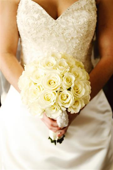 Bride holding white rose bouquet