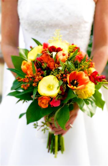 Bride holding yellow and orange flower bouquet