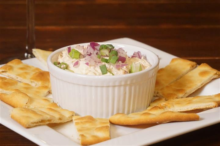 Connemara Salmon Dip. House smoked salmon dip blended with cream cheese, red onions, scallions, horseradish, lemon and sriracha. Served with naan bread and crackers.