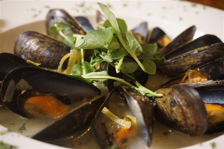 Mussels with white broth in white bowl