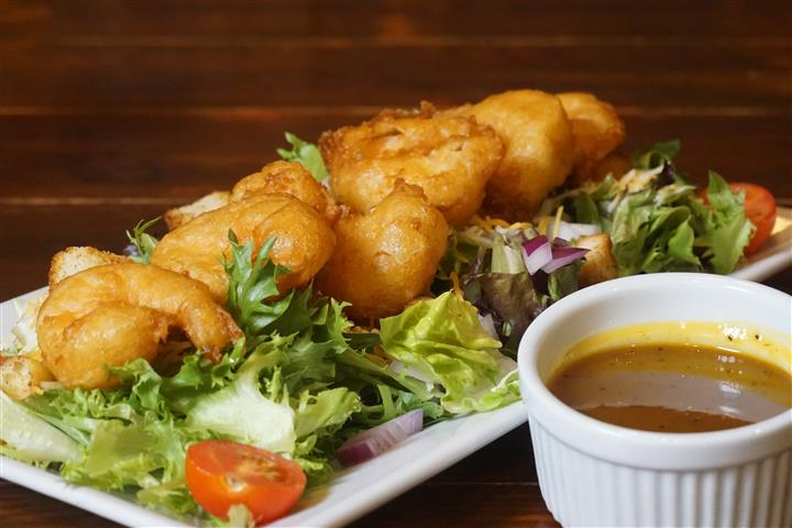 Salad with battered shrimp on white dish and dipping sauce