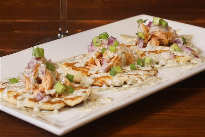 Connemara salmon. House smoked salmon dip blended with cream cheese, red onions, scallions, horseradish, lemon and sriracha. Served with naan bread.