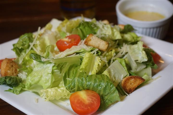 Sisters Salad. Crisp romaine, Parmesan, cherry tomatoes, croutons, house dressing on white dish