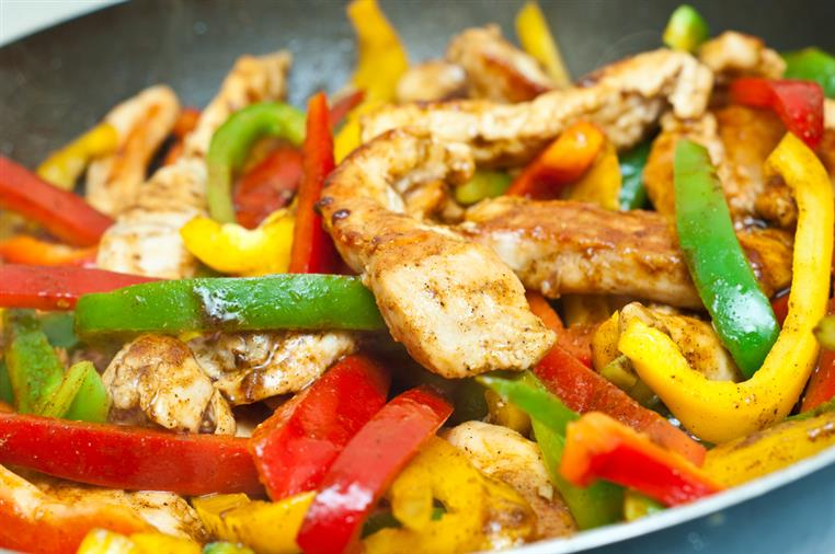 closeup of grilled chicken and slices of peppers in a skillet