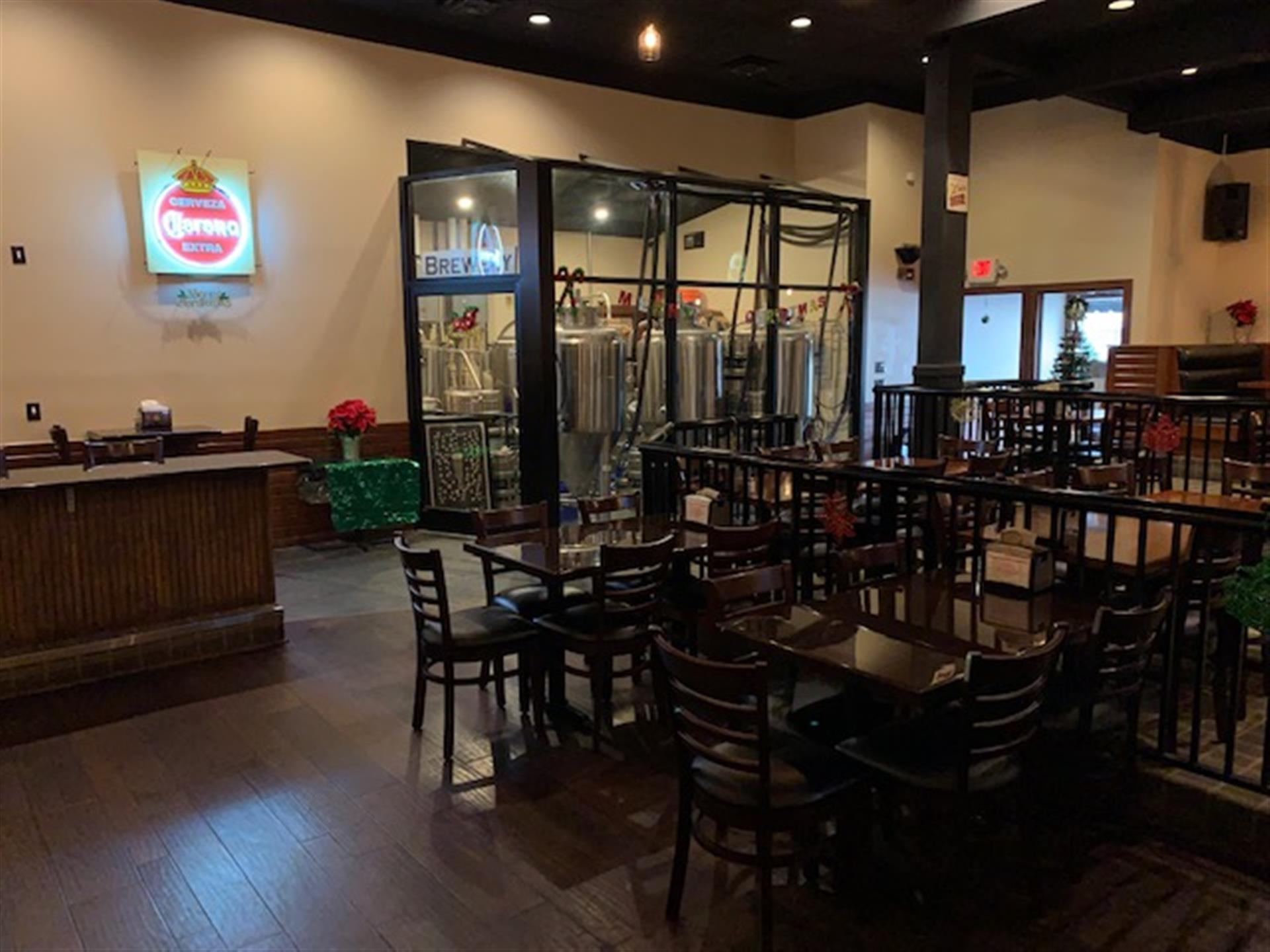 tables and chairs in the event space with an area in the back for the brewing